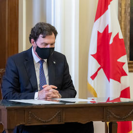 The Administrator reading a document while seated at a table. There is a Canadian flag in the background.