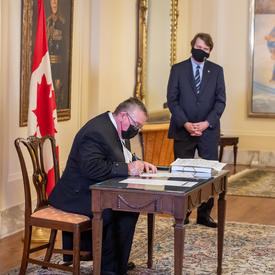 The Administrator and the Secretary looking on as a man signs a document.