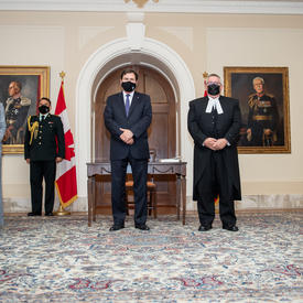 The Administrator is flanked on either side by two people. All five individuals wear masks and maintain physical distancing protocols.