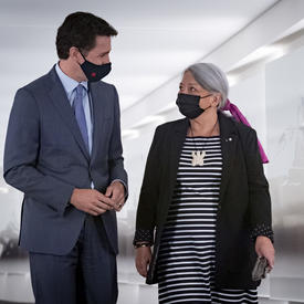 Le premier ministre Justin Trudeau et la gouverneure générale désignée Mary May Simon marchent dans un couloir côte à côte en se regardant.