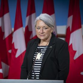 La gouverneure générale désignée Mary May Simon se tient face à un podium devant plusieurs drapeaux du Canada.