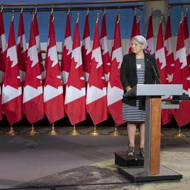 Le premier ministre Justin Trudeau et la gouverneure générale désignée Mary May Simon se tiennent chacun face à un podium devant plusieurs drapeaux du Canada derrière eux.