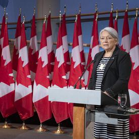 Le premier ministre Justin Trudeau et la gouverneure générale désignée Mary May May Simon se tiennent chacun face à un podium devant plusieurs drapeaux du Canada derrière eux. Mary Simon parle. Justin Trudeau la regarde.