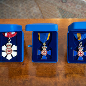 Three Canadian order decorations are positioned on a wood table in individual blue suede boxes. The first decoration is red and white with a red and white ribbon. The second and third decorations are blue with blue ribbon with a yellow border.