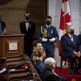 Le secrétaire du gouverneur général occupe le pupitre de la salle du Sénat. Mary Simon et son mari sont assis à sa gauche.