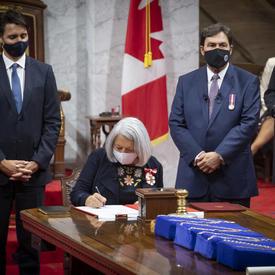 Mary May Simon signe un document au Sénat. Elle est entourée de part et d'autre par le premier ministre et par le juge en chef de la Cour suprême, Richard Wagner.