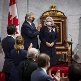 Des personnes au Sénat se tiennent debout en applaudissant Mary May Simon.