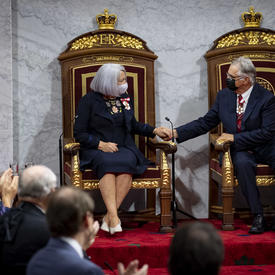 Mary May Simon et son mari sont installés sur des trônes en se tenant la main.