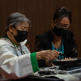 Une Aînée inuite allume le qulliq au Sénat. Une femme est assise à ses côtés.