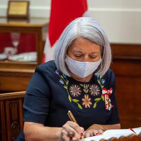 Mary May Simon signe un document.