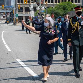 La gouverneure générale Mary May Simon salue la foule alors qu'elle se rend en marchant du Sénat au Monument commémoratif de guerre du Canada.