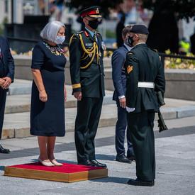 La gouverneure générale Mary May Simon se tient sur une petite plateforme rouge devant le Monument commémoratif de guerre du Canada.