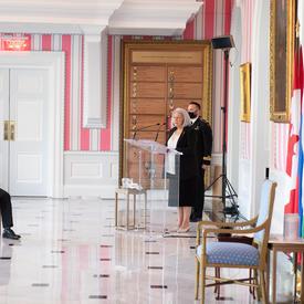 La gouverneure générale Mary May Simon debout derrière un pupitre s'adresse à une audience.