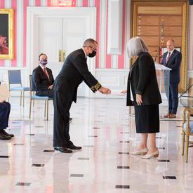 Un homme en costume et portant un masque remet un document à la gouverneure générale.