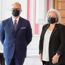 Un homme en costume et portant un masque se tient à la droite de la gouverneure générale Mary May Simon pour la prise d'une photo.