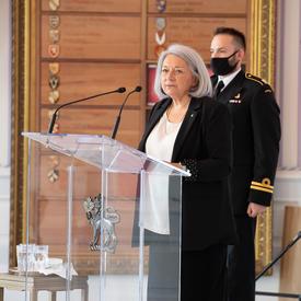 La gouverneure générale s'adresse à une audience depuis un pupitre dans la salle de la tente.