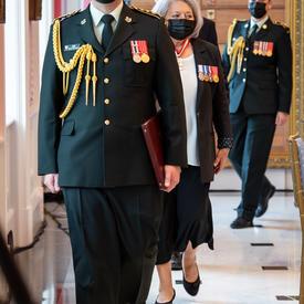 Plusieurs personnes, y compris la gouverneure générale, font leur entrée dans la salle.