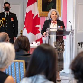 La gouverneure générale Mary May Simon, debout derrière un lutrin en verre, s'adresse au public rassemblé dans la salle de la tente de Rideau Hall. Un imposant drapeau canadien décore le fond de la pièce.