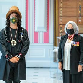 Un homme fraîchement décoré d'une médaille se tient près de la gouverneure générale Mary May Simon. Tous deux portent un masque.