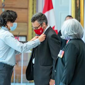 Un jeune homme épingle une médaille sur le veston d'un homme.
