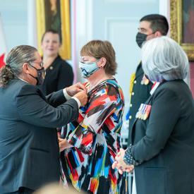 Un homme épingle une médaille sur la robe aux couleurs vives d'une femme.