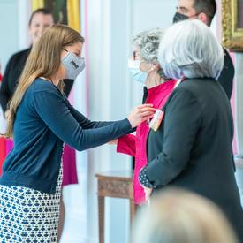 Une jeune femme épingle une médaille sur le blouson fuchsia d'une femme.