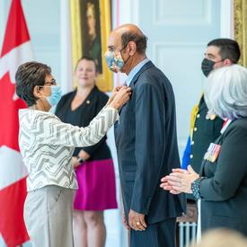 Une femme épingle une médaille sur le veston d'un homme.