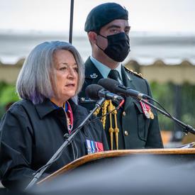 La gouverneure générale Mary May Simon prononce son allocution. Elle est dehors. Un homme en uniforme militaire portant un masque se tient derrière elle. Il pleut.