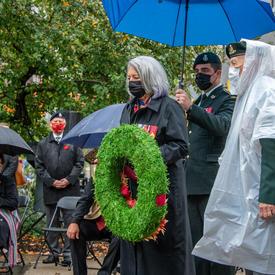 La gouverneure générale dépose une couronne au pied du Monument national aux anciens combattants autochtones. On voit des plumes à la gauche de la photo. Il y a des arbres et quelques personnes portant des masques en arrière-plan.
