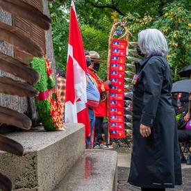 La gouverneure générale dépose une couronne au pied du Monument national aux anciens combattants autochtones. On voit des plumes à la gauche de la photo.
