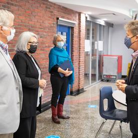 Leurs Excellences parlent avec un employé de la Mission d'Ottawa. Ils portent des masques.