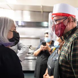 La gouverneure générale parle avec un employé de la Mission d'Ottawa. Ils portent des masques.