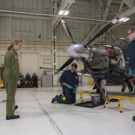 La gouverneure générale s'est entretenue avec des ingénieurs alors qu'ils effectuaient des travaux d'entretien sur un avion.
