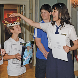 A guide placing a crown on a young guest's head. The guest is holding a picture of the The Queen.