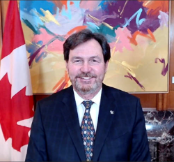 Screenshot of the Administrator smiling at the camera. There is a Canadian flag to his left at a brightly coloured painting behind him.