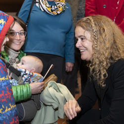 The Governor General, Julie Payette, is squatting to speak to a child wearing a winter coat.