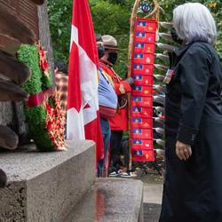 Governor General Mary May Simon is laying a wreath at the base of the National Aboriginal Veterans Monument. Feathers are visible on the left side of the photo. Trees and a small crowd wearing masks are visible in the background.