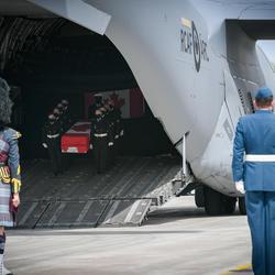 Au premier plan, on voit l'arrière des membres des Forces armées canadiennes (FAC), dont quelqun qui joue de la cornemuse. À l'arrière-plan, nous voyons un cercueil, porté par des membres des FAC, qui descend d'un avion.