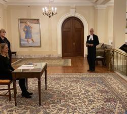La gouverneure générale est assise à un bureau. Sur le côté droit, il y a un homme qui tient un document dans ses mains. Quatre autres personnes sont debout autour du bureau tout en respectant les normes de distanciation sociale.