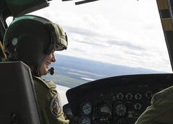 Governor General, sitting in the cockpit, flying a helicopter.