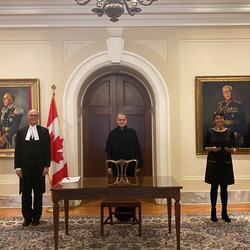 La gouverneure générale est debout derrière une table. Quatre personnes se tiennent de chaque côté d'elle, tout en maintenant les normes de distanciation sociale.