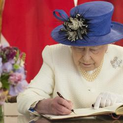 Her Majesty The Queen Elizabeth II is sitting at a table to sign a book.