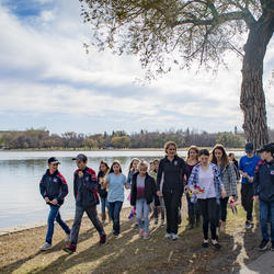 Young group of people walking with the Governor General of Canada with the Saskatchewan legislative building in the background, overlooking the water.