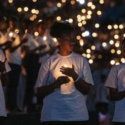 Des centaines de personnes tiennent des bougies.