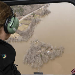 The Governor General is looking at flooded areas from a helicopter.