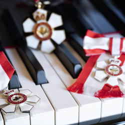 The insignia of the Order of Canada on the keyboard of a piano.