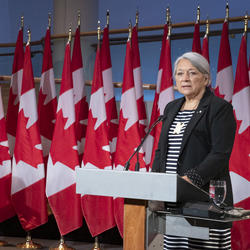 4.Prime Minister Justin Trudeau and Governor General Designate Mary Simon each stand at a podium with several Canadian flags behind them. Mary Simon is speaking. Justin Trudeau's head is turned towards her.