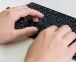 Fingers typing on a keyboard.