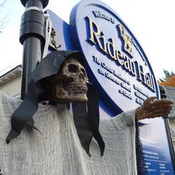 Un costume d'Halloween d'un squelette humain à côté d'un panneau de signalisation de Rideau Hall