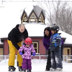 A family of four (2 parents and 2 young children) skating. Winter Pavilion in the background.